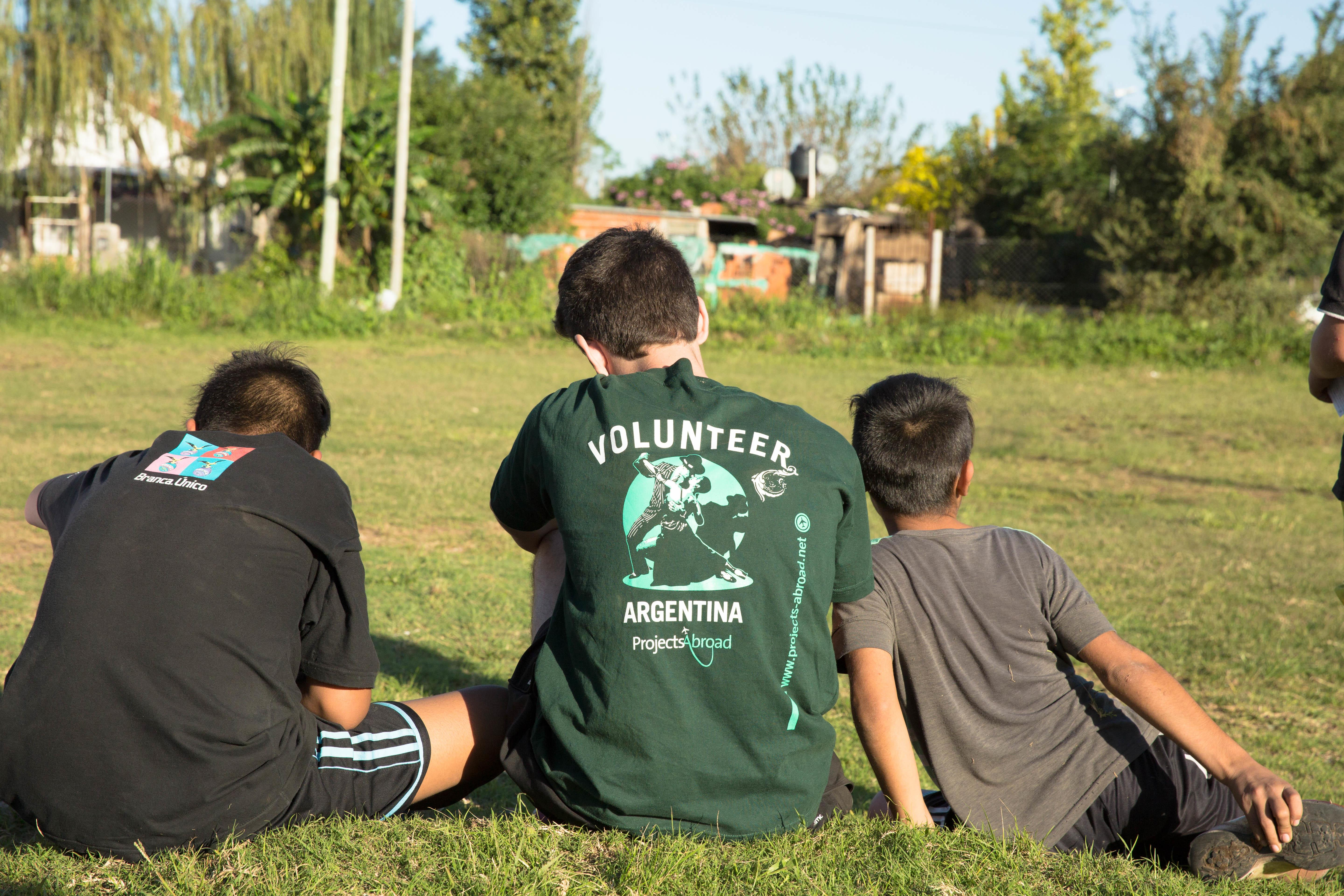 While learning Spanish in Argentina, a student decides to volunteer at a local school and leads an activity outside on the field.